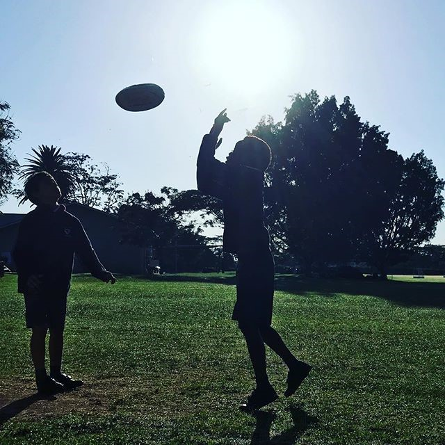 two kids passing a rugby ball on a lawn with the glare of the sun in the background